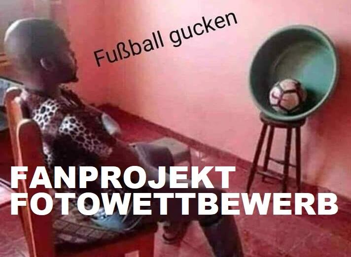 Ein schwarzer Mann betrachtet einen Ball, der vor ihm in einer Schüssel aufgestellt ist, als ob es ein Fernseher wäre. Fußballgucken